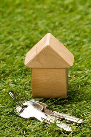 Photo pour Little wooden miniature house model on green grass background with house keys - ecological living or house building concept, selective focus - image libre de droit