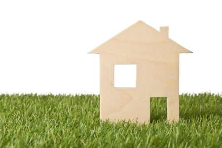 Photo pour Little wooden miniature house model on green grass isolated on white background with copy space - ecological living or house building concept, selective focus - image libre de droit