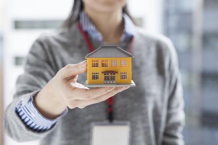 Photo pour Real estate agent woman with a model of the house - image libre de droit
