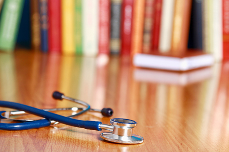 A stethoscope lying  on the desk against books