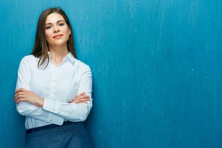 Foto de Smiling business woman with crossed arms portrait on blue wall. White shirt. - Imagen libre de derechos