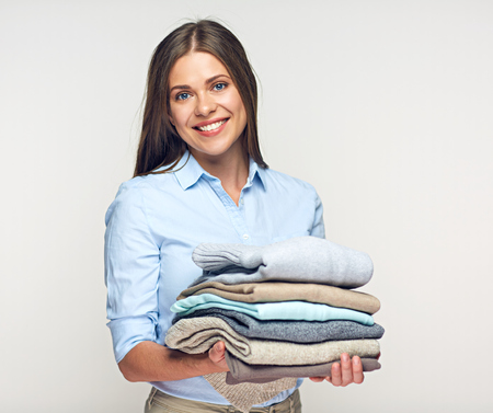 Foto de Smiling woman holding stack of warm winter clothes. Portrait isolated on white. - Imagen libre de derechos