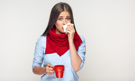 Photo pour Sickness woman holding red cup blow up nose in paper tissue. Isolated portrait on white. - image libre de droit