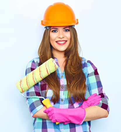 Foto de Young woman with crossed arms holding painting roller, standing against white background wall. Studio portrait of smiling woman. - Imagen libre de derechos