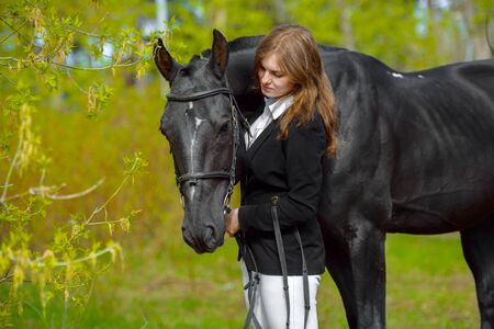 Photo pour Young girl rider with a black horse in the spring outdoors scene - image libre de droit