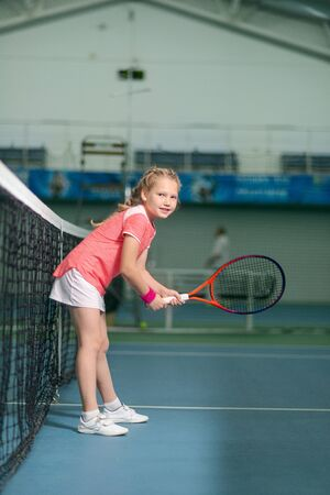 A girl plays tennis on an indoor tennis court. Little girl with tennis racket and ball in sport club. Active exercise for kids. Training for young kid. Child learning to play.