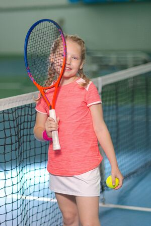A happy playful girl smiles on the tennis court with a racket. Little girl with tennis racket and ball in sport club. Active exercise for kids. Training for young kid. Child learning to play.
