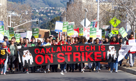Oakland, CA - February 21, 2019: Oakland teachers strike outside of Oakland Technical High School, then marching to city hall. Fighting for smaller class sizes and bigger paychecks.