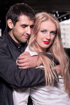 Shoot of glamour young caucasian couple against urban background