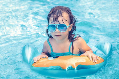 Photo pour Portrait of cute happy little girl having fun in swimming pool, floating in blue refreshing water with rubber ring, active summer vacation on the beach - image libre de droit