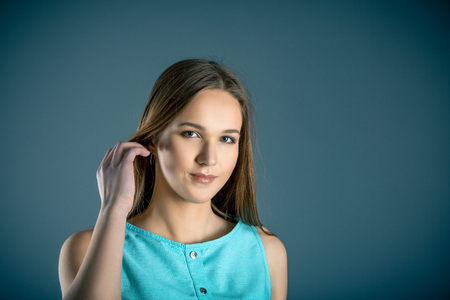 Facial portrait of natural beauty of teen girl looking at camera, small smile over blue grey background