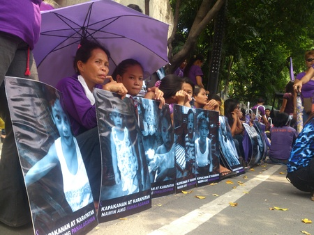 Protest during the oral debate of RH bill at the Supreme Court in Manila. A group of women in violet shirt brings their placard with validation that they are Catholics.