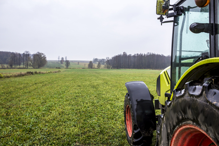 Rainy day in late autumn. Tractor on the edge of a meadow with green grass. Forest in the background. Podlasie, Poland.