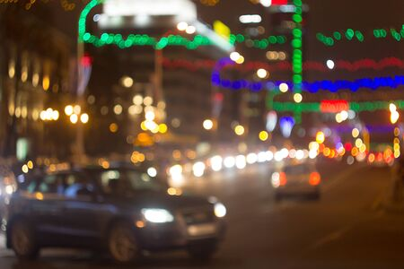 Photo pour Blurred picture of urban illumination in honor of the winter holidays. View of the road, car lights and multi-colored Christmas garlands out of focus. - image libre de droit