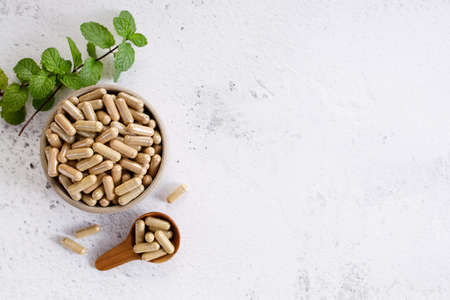Photo pour herb capsules, nutritional supplement, in a small bowl on marble background. alternative healthy lifestyle concept. - image libre de droit