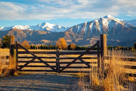 Photo pour A wooden gate that leads to the farm, under the beautiful snow-capped mountains, is closed - image libre de droit