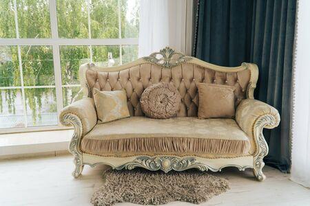 Photo pour beautiful expensive beige sofa against a white wall in an empty room - image libre de droit
