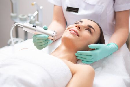 Photo pour Cheerful young lady lying on medical couch and professional beautician conducting oxygen meso therapy - image libre de droit