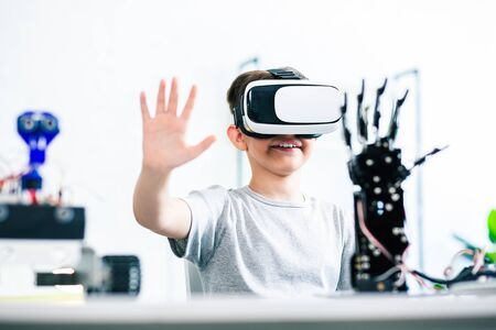 Photo for Cheerful ingenious little boy wearing VR device while experimenting with his robotic creating at home - Royalty Free Image