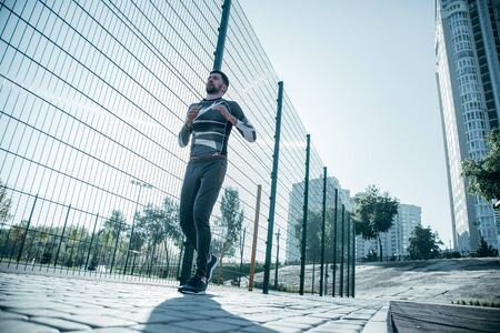 Photo pour Serious sportsman running while having his training outdoors - image libre de droit