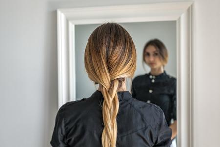 Foto de woman girl with ombre hairstyle in braid in front of mirror - Imagen libre de derechos