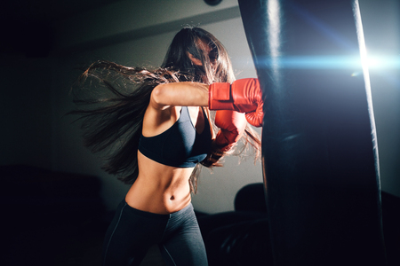 Foto de sexy fighter girl punching actively. motion long hair - Imagen libre de derechos