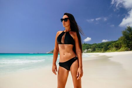 Photo pour luxury woman relax on beach of tropical island. Beach vacation. Long hair beautiful woman happy jump on beach in tropics. Seychelles. - image libre de droit