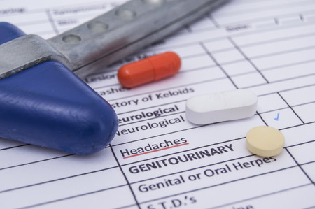 Neurological reflex hammer and colored tablets, pills and capsula lies on a sheet of health history with the words neurological headaches. Treatment of neurological diseases, accompanied by headache