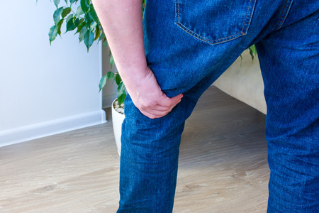 Photo concept pain in popliteal fossa or the back of the knee, knee joints or ligaments, cruciate for example. Man standing with his hand over area, which is located on back of  leg