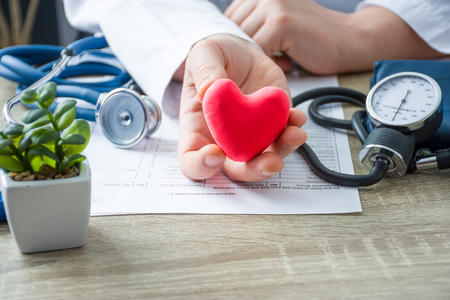 Photo pour Doctor of internal medicine and cardiologist holding in his hands and shows to patient figure of red card heart during medical consultation. Explanation of causes of heart, diagnosis and treatment - image libre de droit