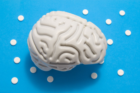 Photo pour 3D anatomical model of brain is on blue background surrounded by white pills as ornament polka dots. Medical concept by pharmacological tablet treating brain diseases, pharmacotherapy, chemotherapy - image libre de droit