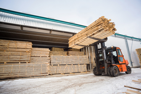 Foto de folk lift truck in wood factory or forestry timber depot - Imagen libre de derechos
