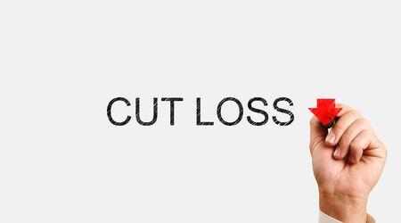 Photo pour Cut Loss concept. male hand writes marker with the words Cut Loss and draws a down arrow - image libre de droit