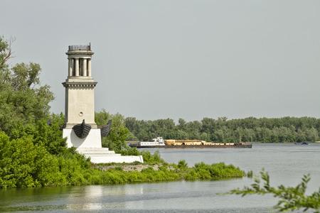 Foto de Old barge Laden with timber floating on the river Volga, past the lighthouse - Imagen libre de derechos