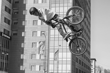 VOLGOGRAD - MAY 24: Young guy in jeans and a t-shirt on a BMX bike performs stunt soaring high in the air. May 24, 2015 in Volgograd, Russia.
