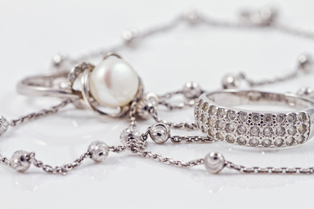 Photo pour Silver ring with precious stones and pearl are together with a silver chain on acrylic - image libre de droit
