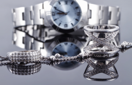 Photo pour Silver rings of different styles and silver chain on the background of reflections women's watches - image libre de droit