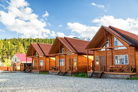 Photo pour Wooden houses of a small comfortable recreation center in the mountains stand in a row against the forest - image libre de droit