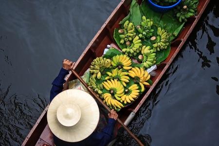 A woman selling fruits at Bangkok floating market.