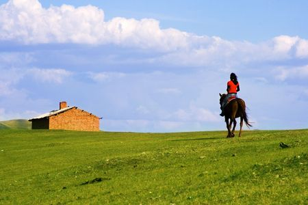 An Asian girl riding a horse returning home.