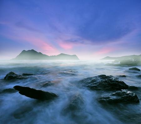 Foto de fantastic landscape with stones in sea water in dusk - Imagen libre de derechos