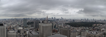 Aerial panoramic view over the cityscape of Tokyo in Japan during daytime with clouds