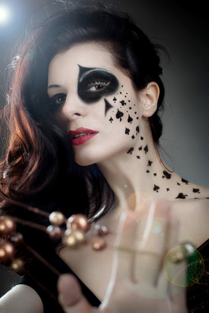beautiful woman with make-up and body-art styled as playing card queens