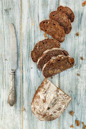 Foto de Freshly baked wheat bread, homemade cakes, still life with bread, crisp loaf of bread, still life on a rustic background, top view, rustic bread, roll, loaf.  - Imagen libre de derechos