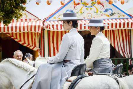 Seville, Spain - April 29, 2015: Pretty amazons wearing traditional Andalusian uniforms at the April's Fair of Seville. The Seville Fair Feria de abril de Sevilla is one of most important celebration of the city, it begins one or two week after easter H