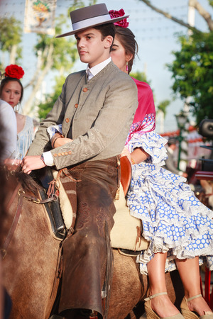 Seville, Spain - April 23, 2015: Couple in traditional dress riding at the April Fair Seville. The Seville Fair Feria de abril de Sevilla is one of most important celebration of the city, it begins one or two week after easter Holy Week