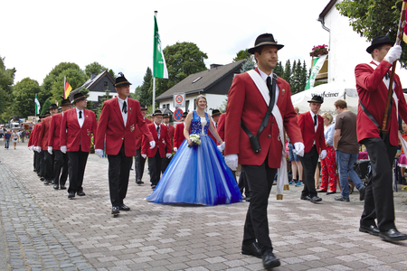 Usseln, Germany - July 29th, 2018 - Rifle club members parading in their traditional red uniforms at the marksmen's fair with the reigning champion's wife in formal blue dress in the middle
