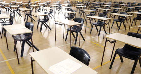 A view looking down on a large secondary high school exam hall set up with organized desks table and papers ready for students to sit the examination.