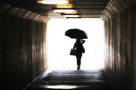 Photo for Highly saturated silhouette of a confident woman holding an umbrella exiting a tunnel. Wet weather working city chic lifestyle. Weather forecast, rain and showers. Leaving arriving confidence concept - Royalty Free Image