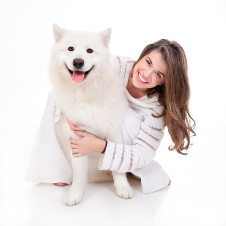 a studio image of a young woman, dressed in white, with her white dog, huging it, both posing, looking happy and smiling